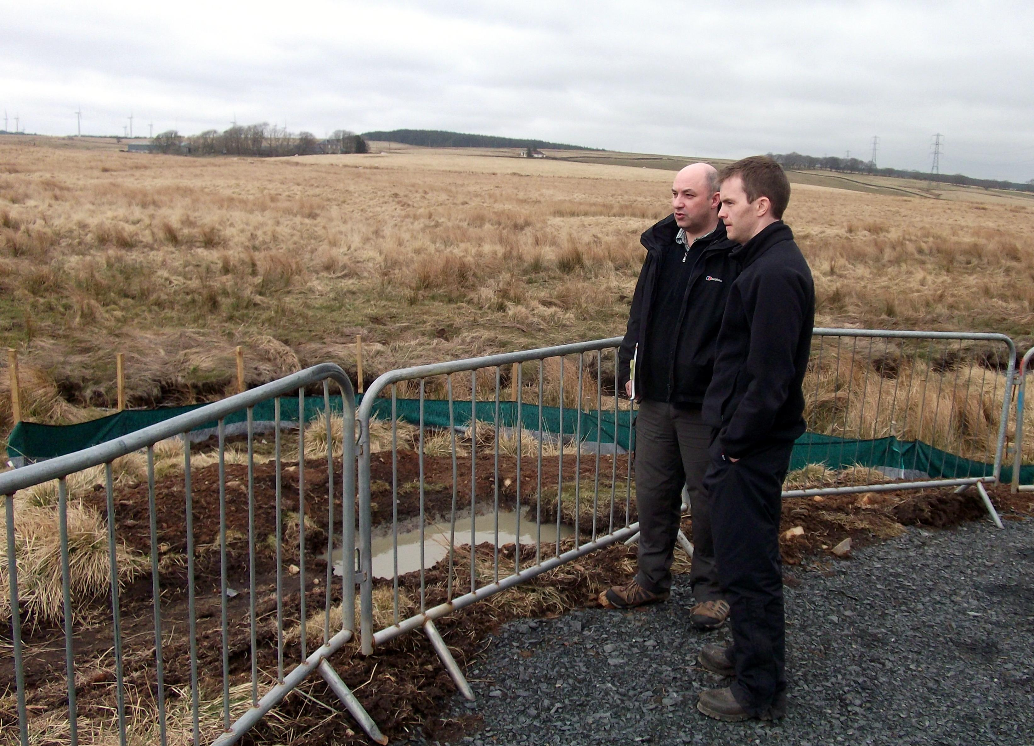Pic3. Roddy talks to Richard McMullan of Eco-Fish Consultants about the groundworks at the West Browncastle Wind Farm site (note: the small sediment lagoon + silt fencing that has been engineered at the base of the temporary site compound)